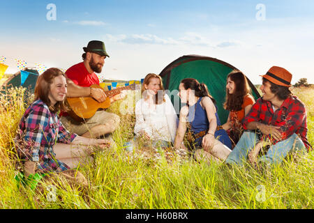 Young people singing to the guitar at campsite - Stock Photo