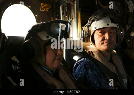 Japanese Maritime Self-Defense Force Rear Adm. Hiroshi Yamamura waits in an MV-22 Osprey helicopter to depart the - Stock Photo