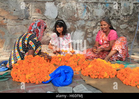 Preparing Marigold garlands for Diwali, the Hindu Festival of Lights, Delhi, India, Indian subcontinent, South Asia - Stock Photo