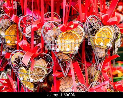 Many gifts hanged in a market stall of a Christmas little market in Austria, decorated with dried fruits. - Stock Photo