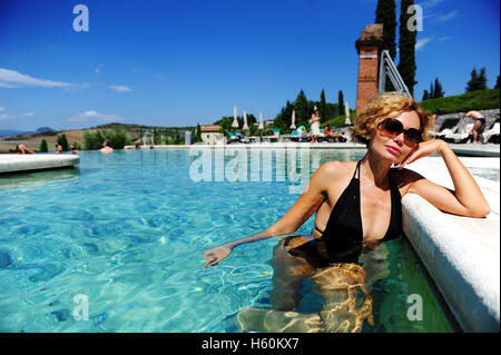 woman relaxing in the thermal outdoor pool of the fonteverde natural spa resort in san casciano