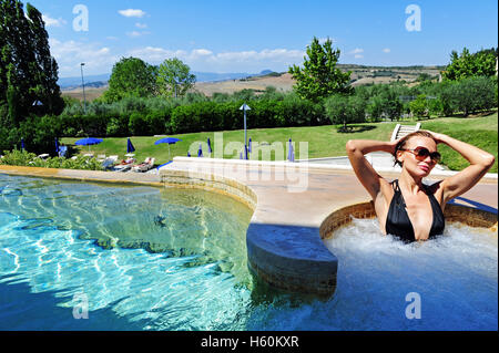 a woman relaxing in the jacuzzi of the fonteverde natural spa resort in san casciano dei
