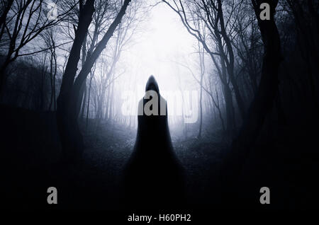 scary cloaked figure in dark scary forest Halloween landscape - Stock Photo