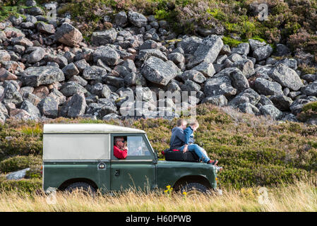 Two kids on hood of old 4x4 Land Rover jeep driving in the mountains - Stock Photo