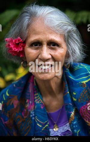 Rarotonga Island. Cook Island. Polynesia. South Pacific Ocean. An elderly woman dressed in modern suits of Polynesian. - Stock Photo