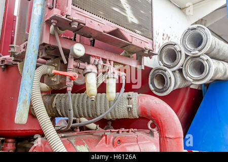 View on truck compressor, water hose with couplings piled on the sewage truck, suction or discharge hose. - Stock Photo