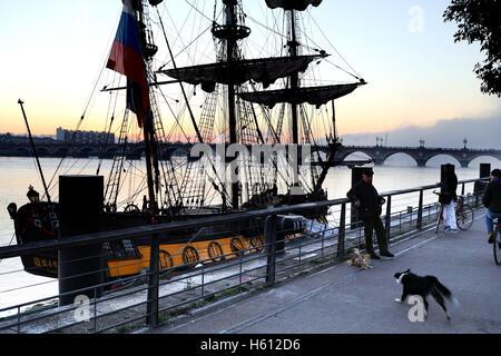 Old Russian clipper moored on Garonne river in front of stone bridge Pont de Pierre - Stock Photo