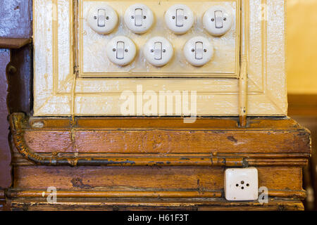 Seven old light switches placed on a wall of an old house. These objects are used to turn off and turn on the light, - Stock Photo