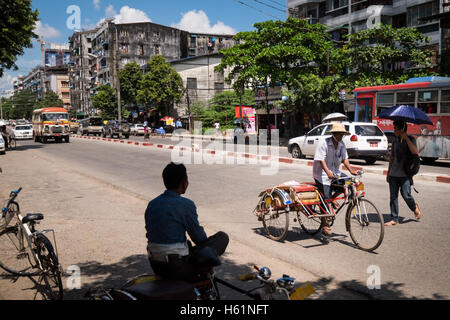 A man on a tricycle bike riding in a street in Yangon, Myanmar - Stock Photo