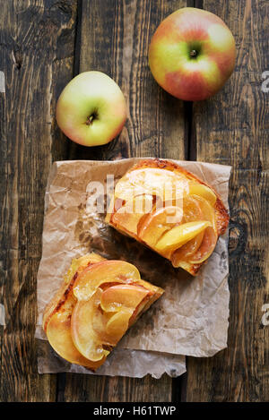 Caramelized apples on toast bread over wooden background, top view