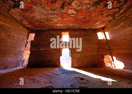 Light streaming through the windows of the Urn Tomb of the Royal Tombs in the rock city of Petra, Jordan - Stock Photo
