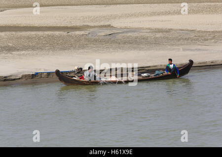 Two fishermen setting a net from a small boat next to the bank of the Irrawaddy River in Myanmar (Burma). - Stock Photo