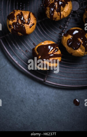decorating profiteroles with melted hot chocolate on cooling rack - Stock Photo
