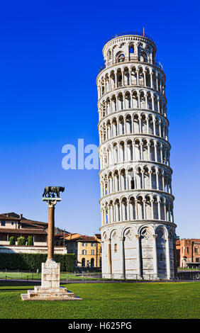 Tall but leaning tower of Pisa in a Miracoli architecture complex with straight wolverine column against blue sky. - Stock Photo
