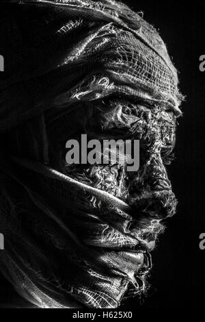 Male model in mummy zombie costume with papier mache, bandages / Camouflage soldier, monochrome, black and white - Stock Photo