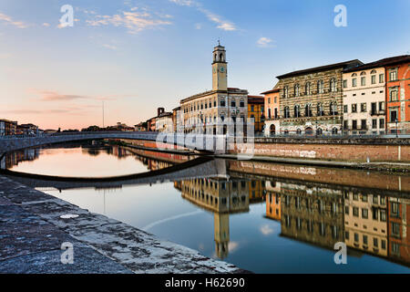 Colourful residential houses along Arno river in the downtown of Pisa - famous historic Italian city. Still waters - Stock Photo