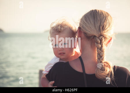 Child with a sincere look hugging his mother sitting on her hands and looking at camera. Mother holding her baby - Stock Photo