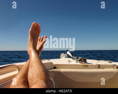 Put your feet up - a pair of feet on the front of a boat with a blue sky behind, on the Caribbean Sea at Barbados - Stock Photo