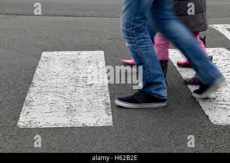 In the street, children crossing a crosswalk - Stock Photo