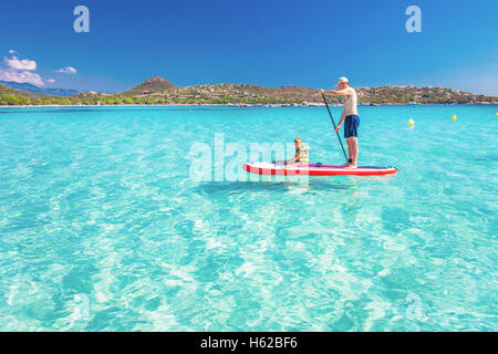 Father with his little happy son having fun on stand up paddle board on Corsica island, France. - Stock Photo