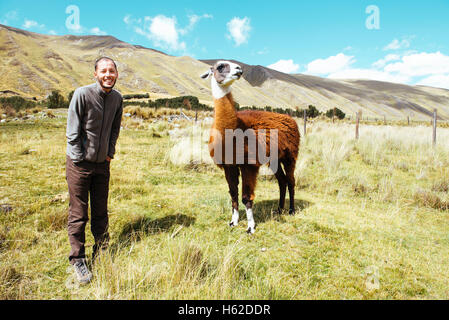 Peru, Huaraz, traveler with a llama in a meadow - Stock Photo