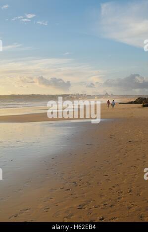 Distant figures walking on beach in the golden evening light