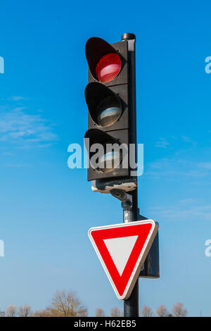 red traffic light with yield sign on blue sky - Stock Photo