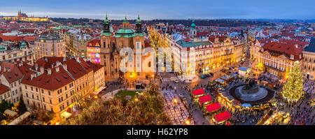 Panoramic view from above of city skyline, illuminated buildings and traditional Christmas market in Prague. - Stock Photo