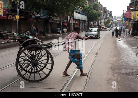 A Hand Pulled Rickshaw passing  on  Tram line street kolkata west Bengal India - Stock Photo
