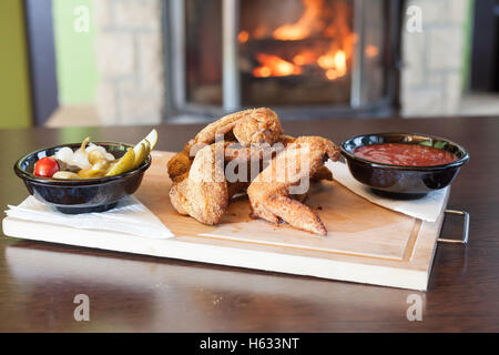 Closeup of roasted chicken wings with vegetables and a delicious sauce. Served on a wooden cutting board. In the - Stock Photo