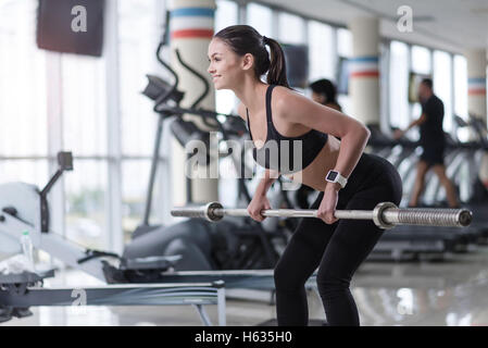 Slim girl doing barbell squat in a gym - Stock Photo