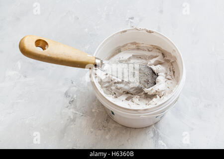 metal spatula with wooden handle in tube with putty on the concrete floor - Stock Photo