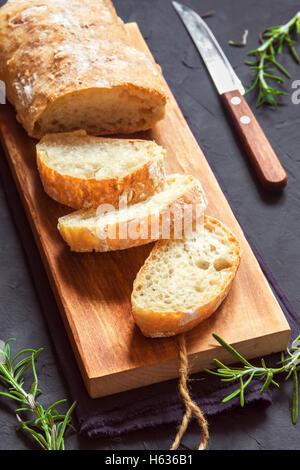 Italian bread Ciabatta and rosemary on black background - fresh homemade bread bakery - Stock Photo