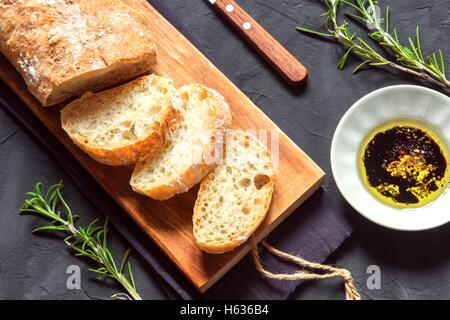 Italian bread Ciabatta with olive oil and rosemary on black background - fresh homemade bread bakery - Stock Photo
