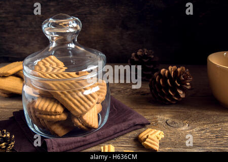 Homemade spicy ginger cookies in glass jar over rustic wooden table, tasty winter ginger pastry - Stock Photo