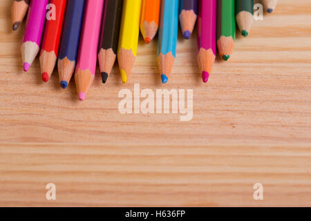 coloured pencils on the wooden background - Stock Photo