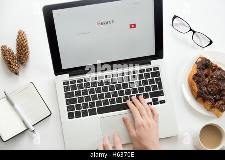Hands working on a laptop, glasses, notebook, cones, office supplies - Stock Photo