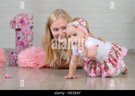 Happy one year old girl with her young and beautiful mother - Stock Photo