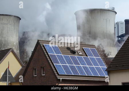 Contrasting sources of energy: a solar electric (pv) generating system on a house roof next to a coal power station, - Stock Photo