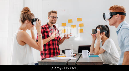 Business people using virtual reality goggles during meeting. Team of developers testing virtual reality headset and discussing