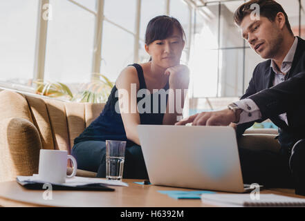 Shot of young woman sitting with businessman pointing at laptop screen. Business partners working together on laptop - Stock Photo