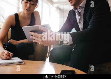 Cropped image of businessman holding digital tablet and woman with notepad. Businesspeople sitting in lobby working - Stock Photo