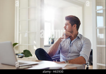 Shot of young man sitting at table looking away and thinking. Thoughtful businessman sitting home office. - Stock Photo