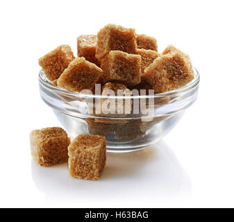 Brown cane sugar cubes in glass bowl isolated on white background - Stock Photo