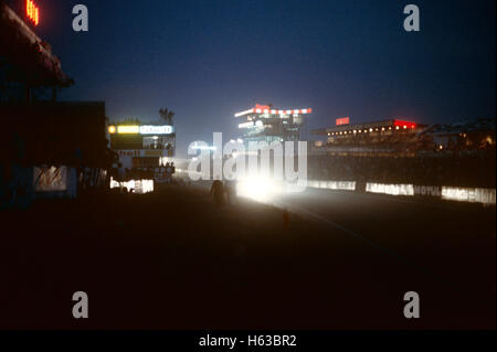 Headlights of a car racing up the start finish straight at night at Le Mans 1980s - Stock Photo