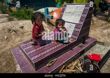 Chichicastenango, Guatemala - April 24, 2014: Children sitting in a grave in the cemetery of the town of Chichicastenango - Stock Photo
