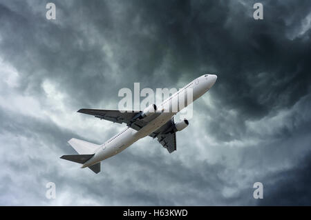airplane on impressive pattern of clouds before a rain - Stock Photo