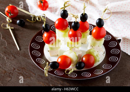 Greek salad with fresh vegetables, feta cheese and olives. Appetizer canape on the holiday table. - Stock Photo