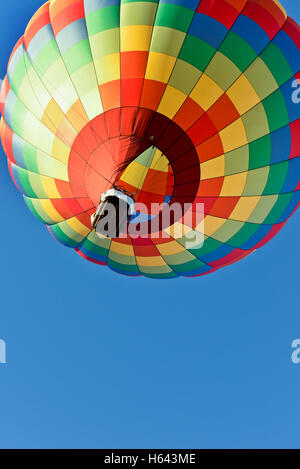 A hot air balloon rising with bright  blue sky - Stock Photo