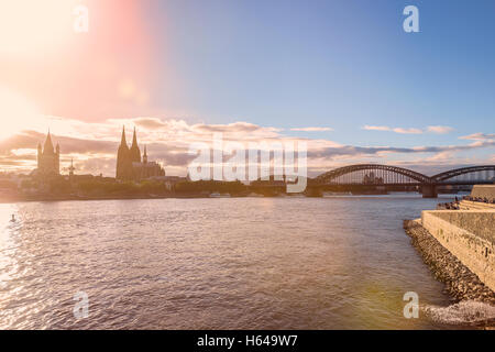 Germany, Cologne, view to the city with Rhine River in the foreground at evening twilight - Stock Photo
